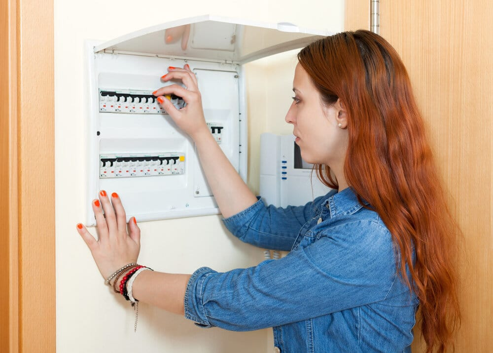 homeowner flipping circuit breakers on her electrical panel